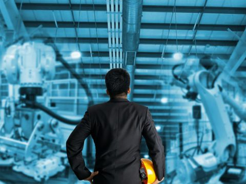 A process engineer examining robot performance in a factory
