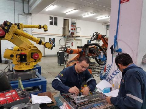 Two people working alongside robots